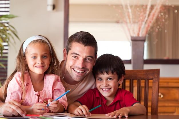 Pai radiante ajudando os filhos para a lição de casa