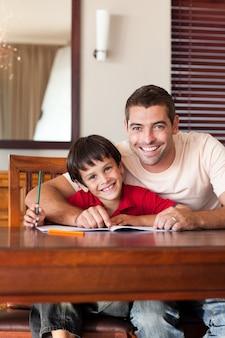Pai radiante ajudando seu filho a fazer a lição de casa