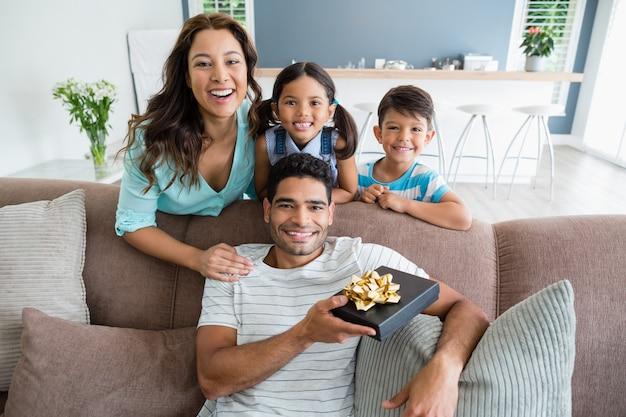 Pai recebendo um presente de seus filhos e esposa na sala de estar