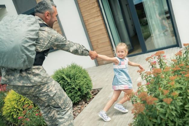 Pai saindo. rapariga loira se sentindo infeliz enquanto o pai servia como militar saindo por meio ano