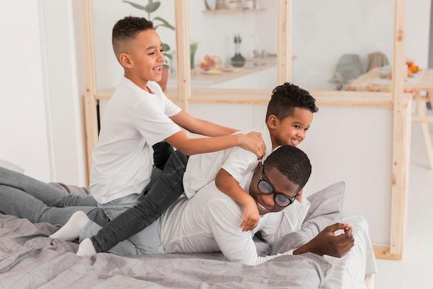 Pai se divertindo com seus filhos na cama
