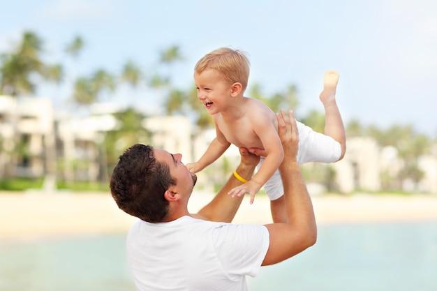 Pai se divertindo na praia com seu filho pequeno