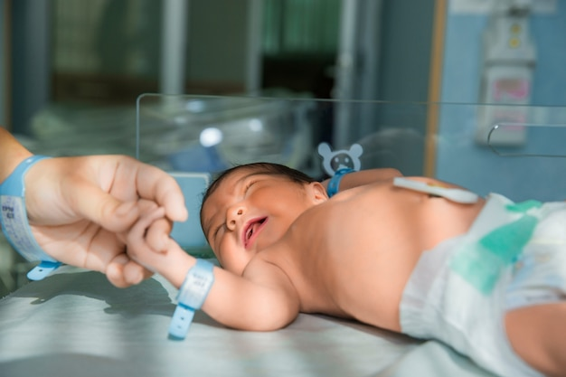 Pai segura a mão do bebê recém-nascido em fraldas