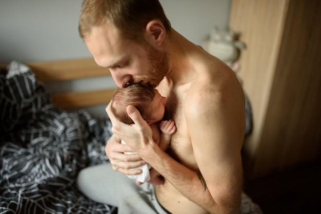 Pai segura nos braços o filho recém-nascido.