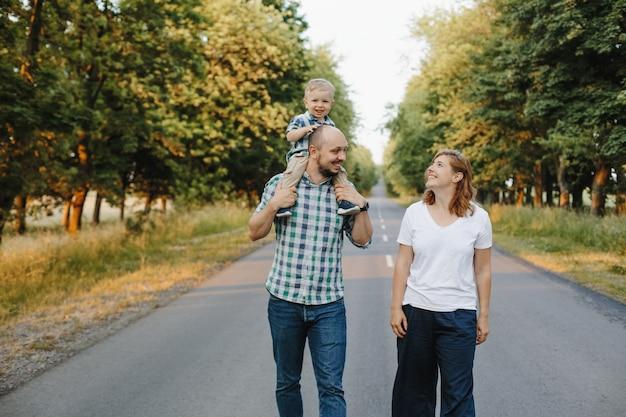 Pai segura um filho nos ombros, uma mãe fica perto, eles sorriem