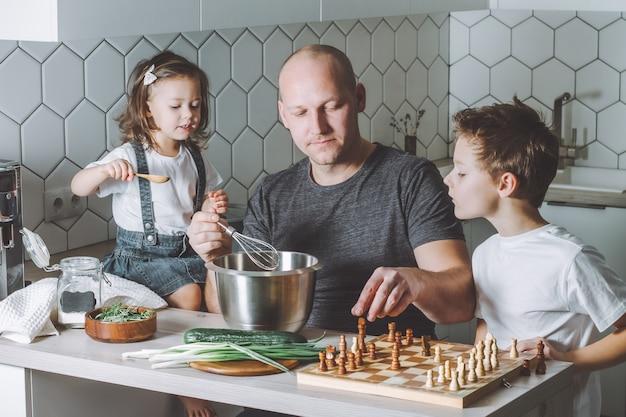 Pai segura um sussurro, jogando xadrez com o filho e conversando com a filha. homem fazendo tarefas domésticas.