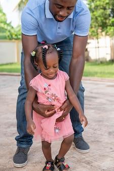 Pai segurando a filha enquanto caminha