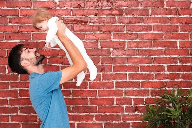 Pai segurando bebê com planta de canto