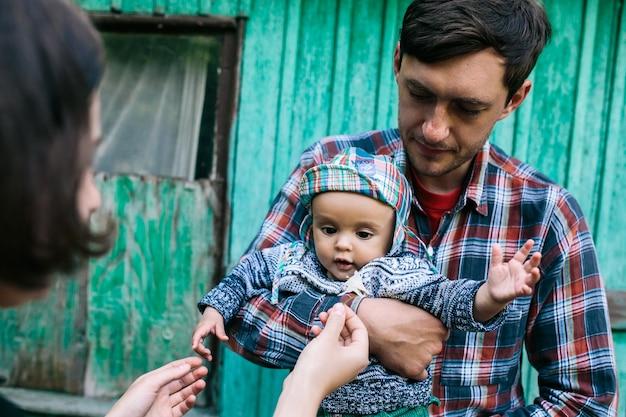 Pai, segurando, bebê, ficar, exterior, casa