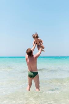 Pai, segurando, criança, em, a, litoral