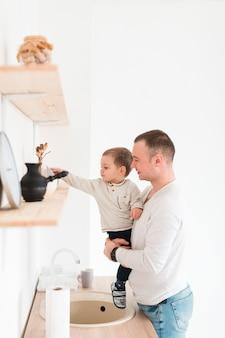 Pai, segurando, criança, enquanto, cozinha