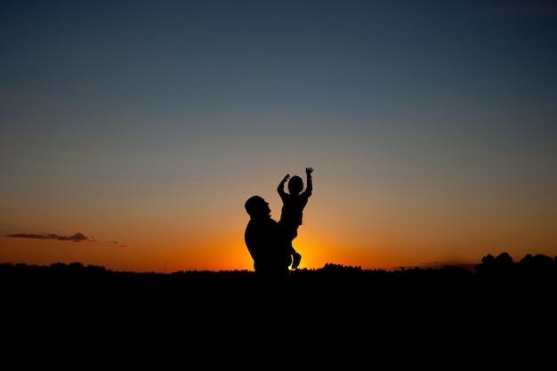Pai segurando e levantando sua silhueta de criança