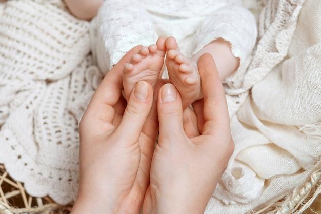 Pai segurando nas mãos os pés do bebê recém-nascido