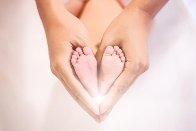 Pai segurando nos pés do bebê recém-nascido.