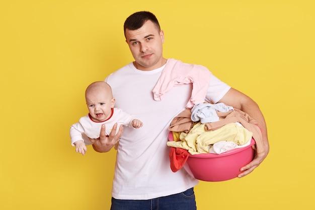 Pai segurando o bebê recém-nascido e a bacia com roupas sujas, pai em licença paternidade, fazendo tarefas domésticas e passando um tempo com a filha, isolado sobre a parede amarela.