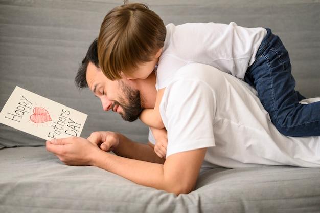 Pai segurando o cartão no sofá