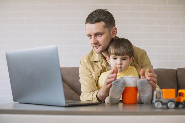 Pai segurando o filho e trabalhando em casa
