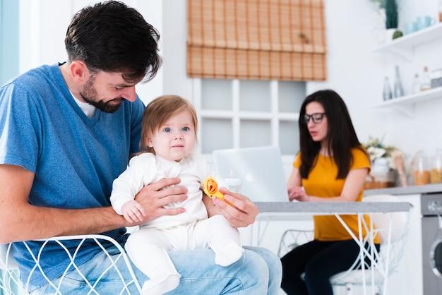 Pai, segurando o filho na cozinha