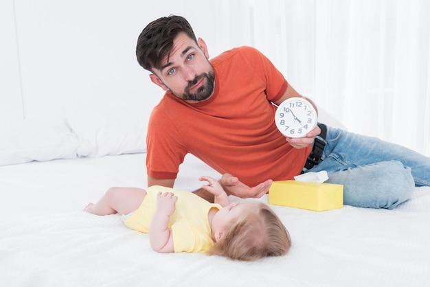 Pai segurando o relógio ao lado do bebê na cama