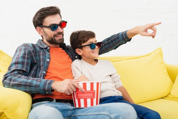 Pai segurando pipoca e assistindo a um filme com seu filho