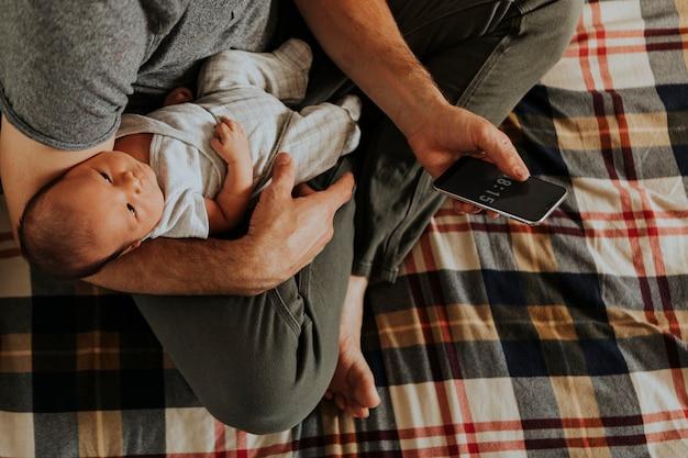 Pai, segurando, seu, bebê, enquanto, usando, seu, telefone
