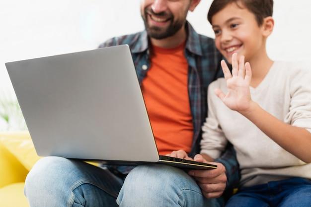 Pai segurando um laptop e criança saudando