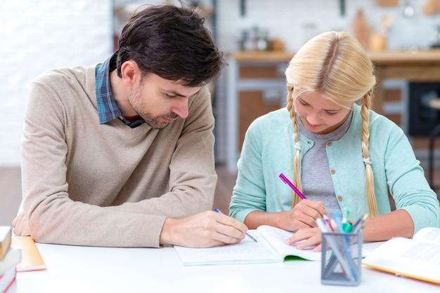 Pai sendo um tutor para sua filha e ensinando-a