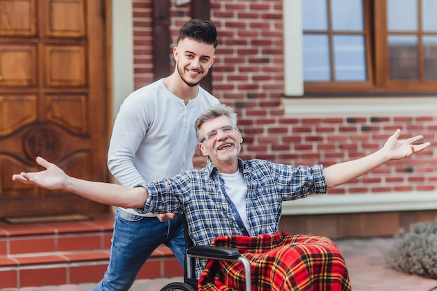 Pai sênior em cadeira de rodas e filho pequeno em uma caminhada