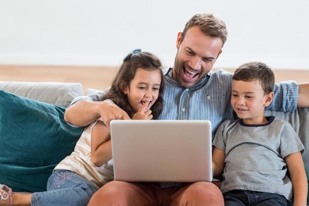 Pai sentado com filho e filha e usando o laptop