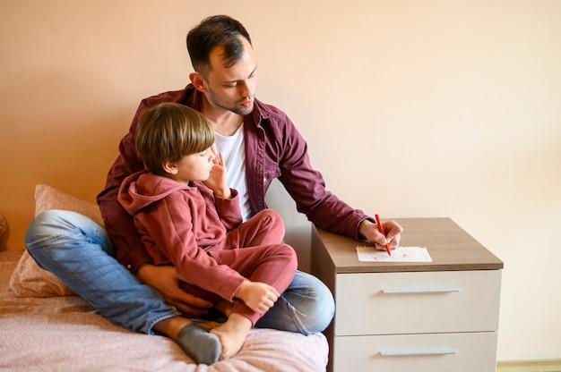 Pai sentado com o filho na cama