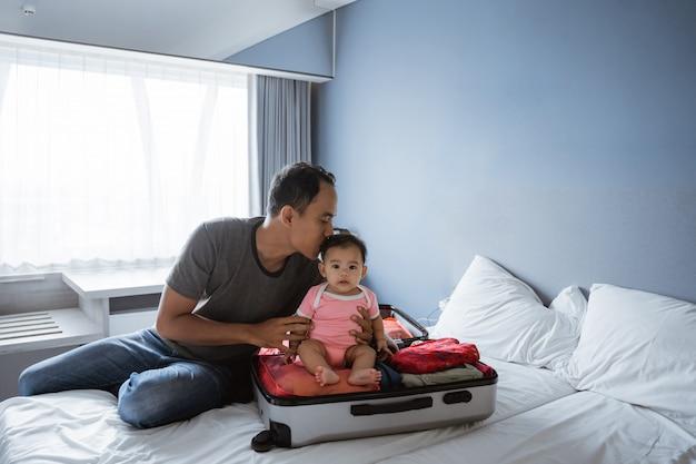 Pai sentado segurando e beijando um bebê que estava sentado em uma mala aberta