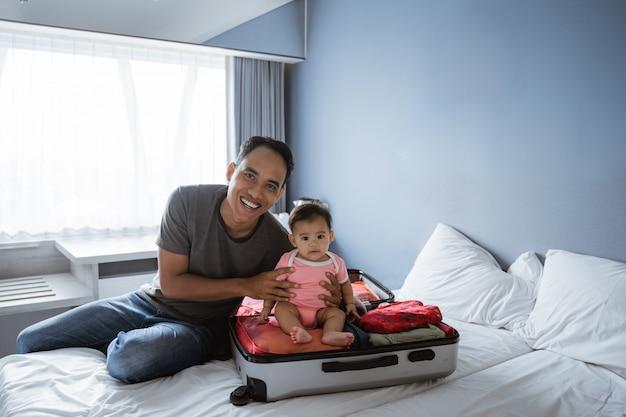 Pai sentado segurando um bebê e sorrindo