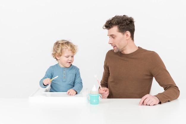 Pai, sentando, tabela, e, alimentação, seu, menino bebê, filho
