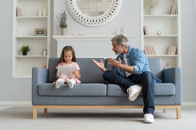 Pai sério repreendendo a filha no interior de casa.
