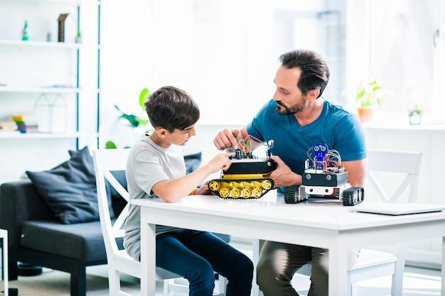 Pai simpático e seu filho inteligente experimentando com seus robôs enquanto se divertem com a engenharia
