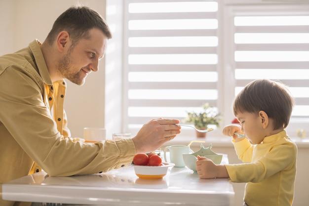 Pai solteiro e criança tomando café da manhã