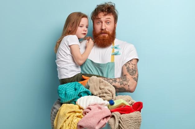 Pai solteiro raposa e ocupado tenta provocar criança chorando, olha com expressão intrigada, usa avental, lava roupa, tem muito trabalho doméstico, isolado sobre parede azul. paternidade e conceito de negócio