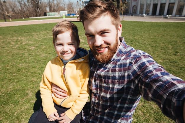 Pai sorridente barbudo ao ar livre com seu filho pequeno