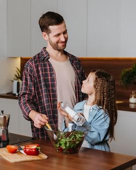 Pai sorridente com filha preparando comida na cozinha