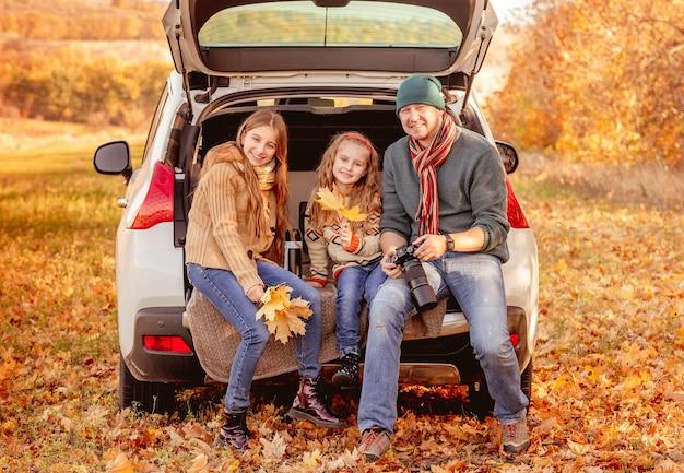 Pai sorridente com filhas em ambiente de outono