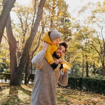 Pai sorridente com seu bebê ao ar livre na natureza