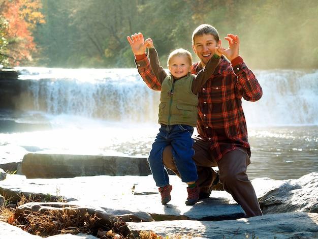Pai sorridente com seu filho em um parque cercado por vegetação e uma cachoeira sob o sol