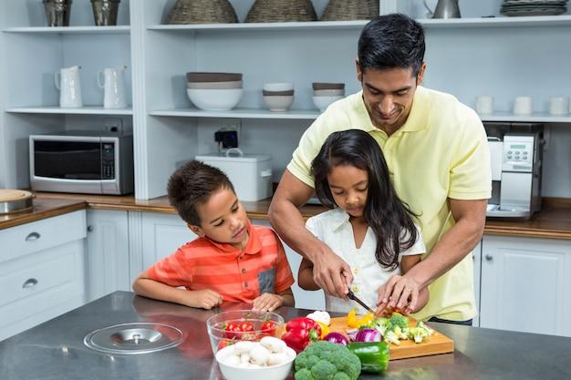 Pai sorridente cortando legumes com seus filhos