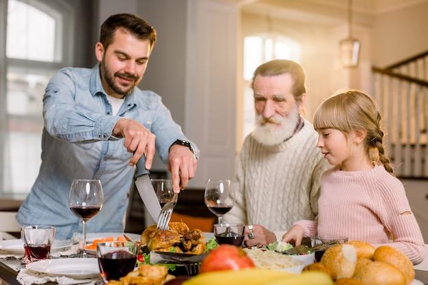 Pai sorridente cortar fatias de peru para jantar em família