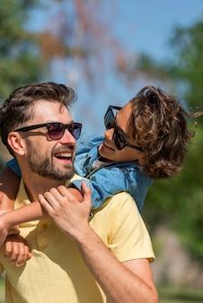 Pai sorridente e filho passando um tempo juntos no parque