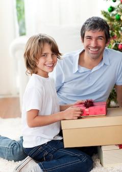 Pai sorridente e seu filho abriram presentes de natal