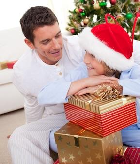 Pai sorridente e seu filho desempacotando presentes de natal