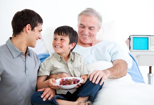 Pai sorridente e seu filho visitam o avô