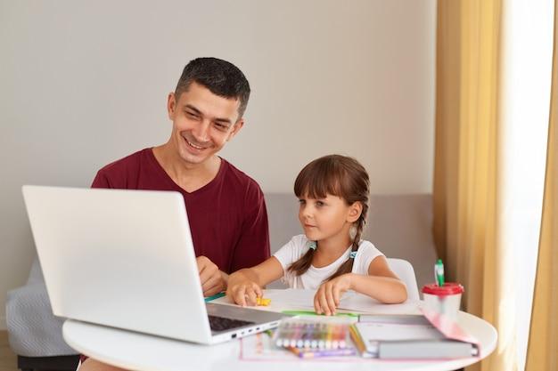 Pai sorridente e uma filha fazendo lição de casa em casa, sentados à mesa na sala, olhando para a tela do laptop com sorrisos, tendo emoções positivas, educação online.
