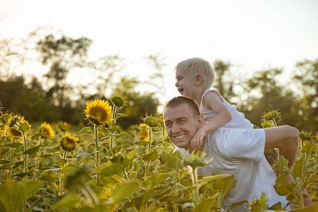 Pai sorridente feliz com o filho nas costas, andando em um campo verde de girassóis florescendo